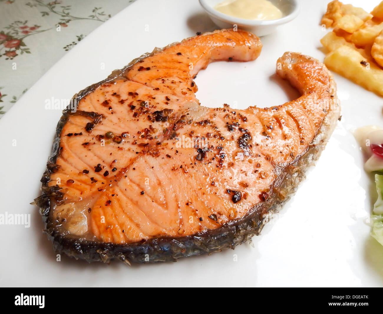 Salmon Steak on white dish - Stock Image