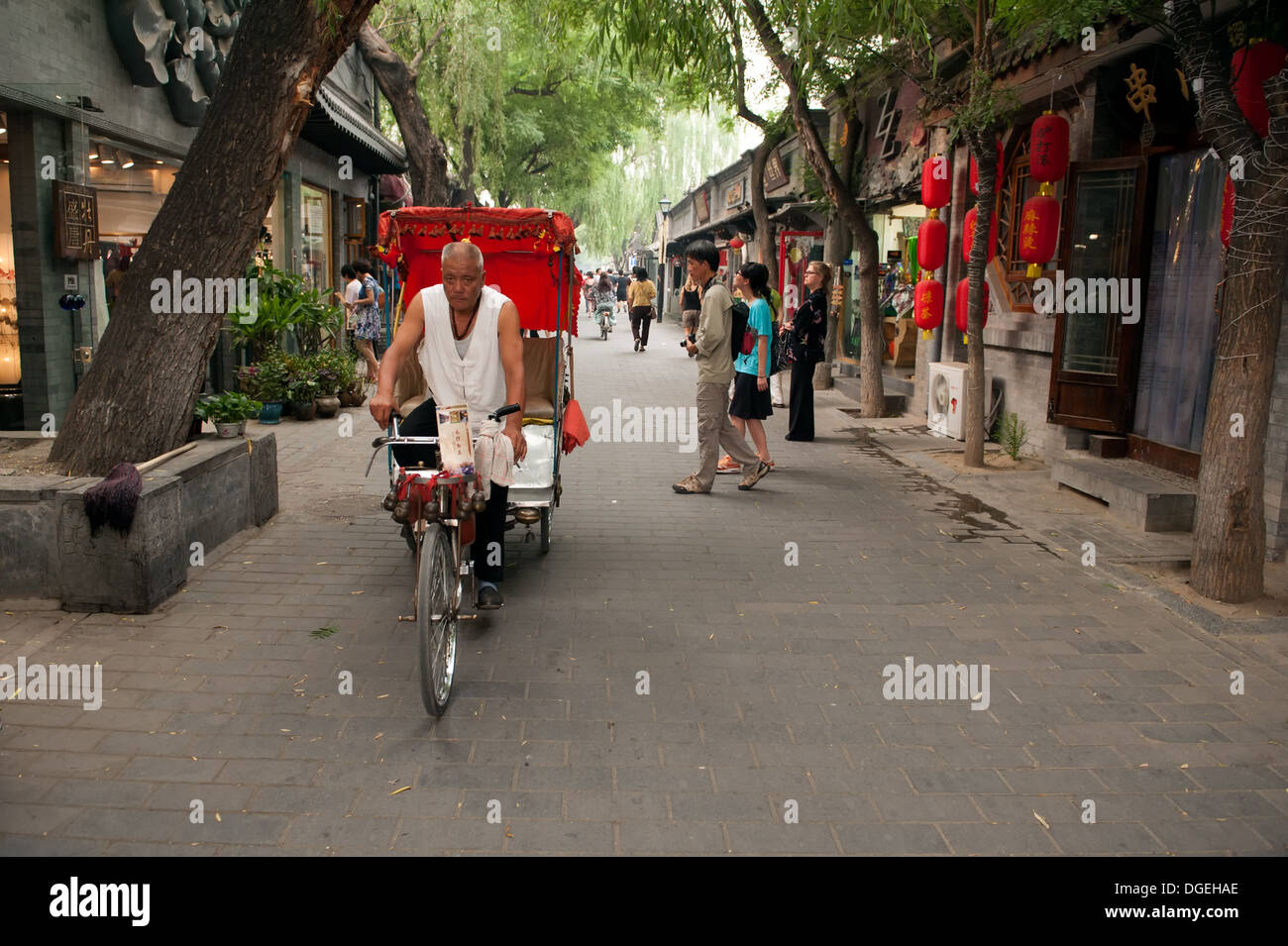 Traditional rickshaw on the main street in the Jing Yang Hutong of Beijing. The Hutongs provide a glimpse of life in Beijing. - Stock Image
