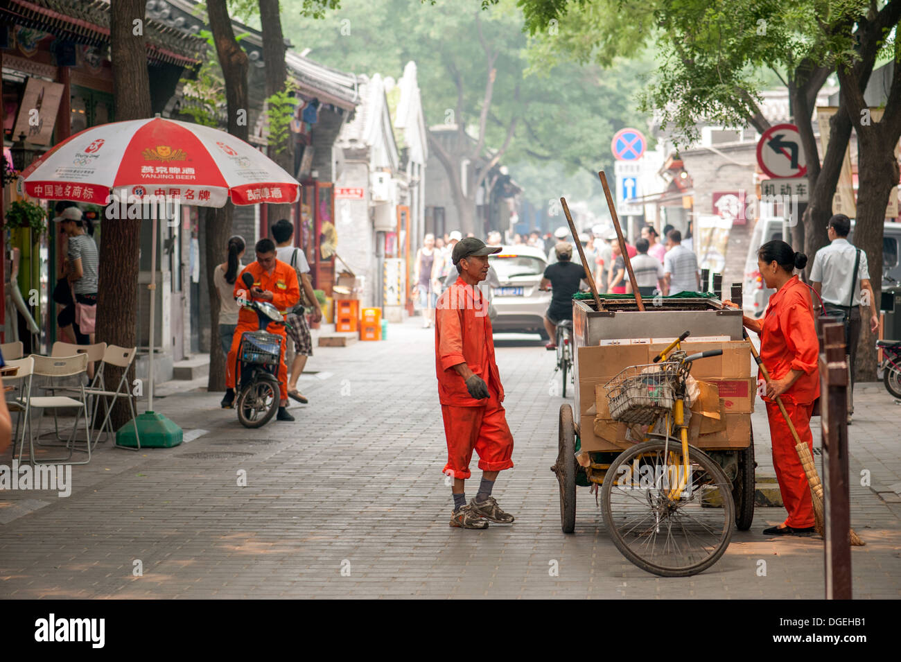 Sanitation workers cleaning the main street in the Jing Yang Hutong of Beijing. The Hutongs provide a glimps of life in Beijing. - Stock Image
