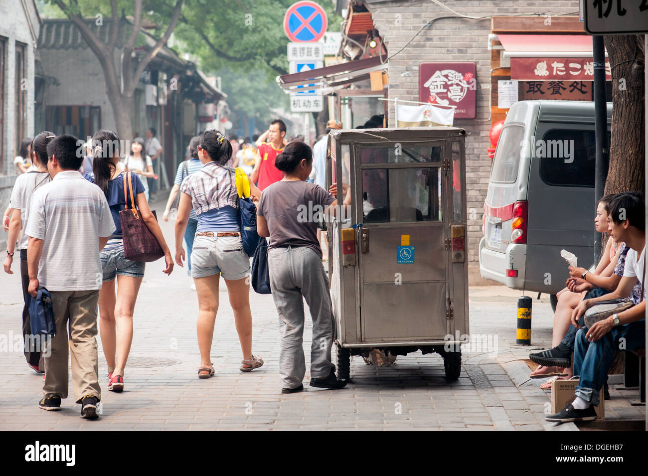 Chinese woman catches a tiny bicycle taxi on the main street in the Jing Yang Hutong of Beijing. - Stock Image