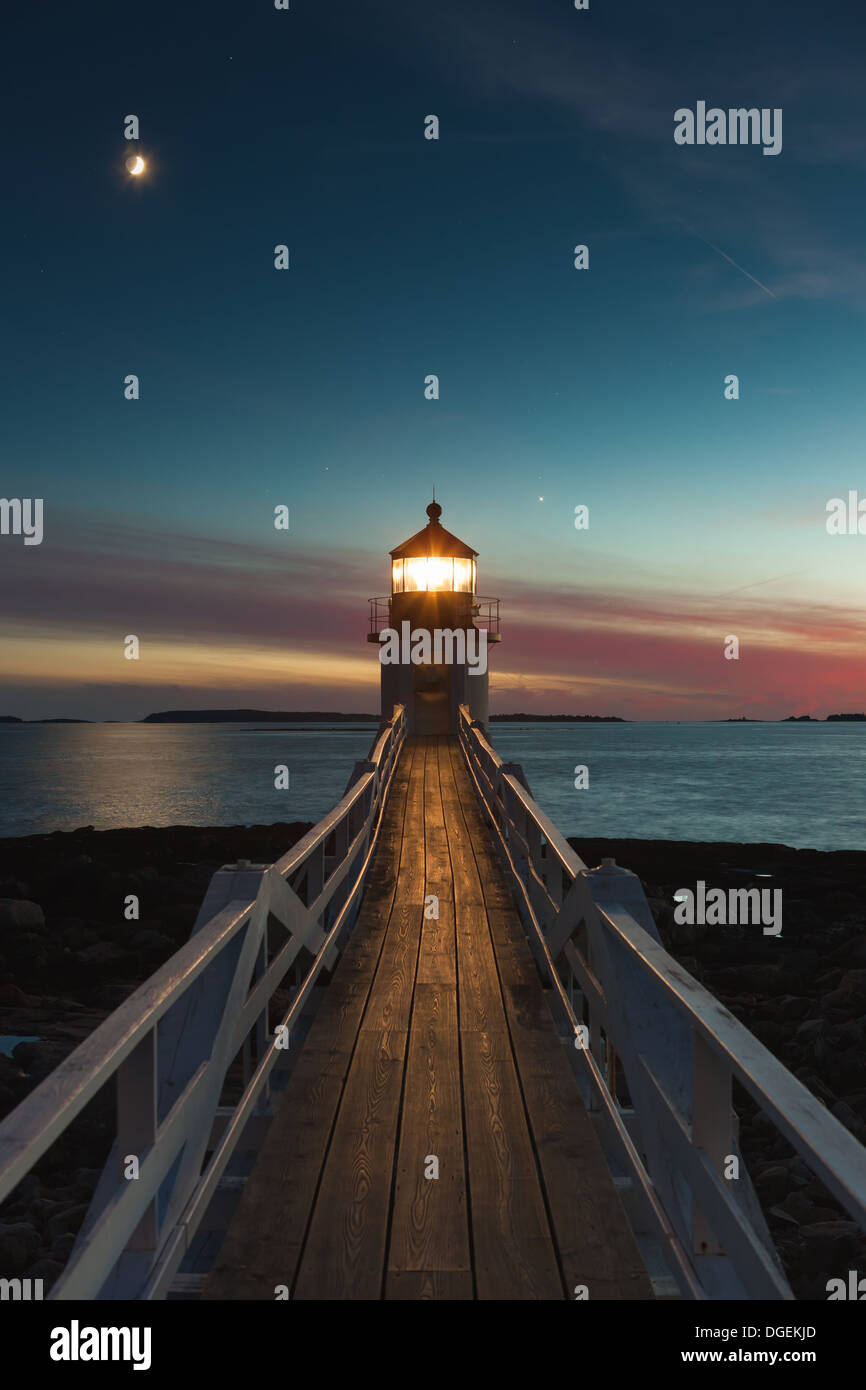 Marshall Point Lighthouse shines into the evening sky under a waxing crescent moon over Port Clyde Harbor in Port Clyde, Maine. - Stock Image