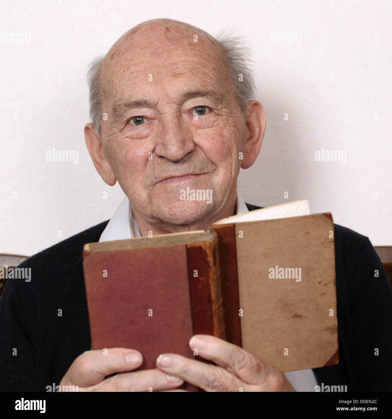 Portrait of a grandpa reading fairy tales from an old book - Stock Image