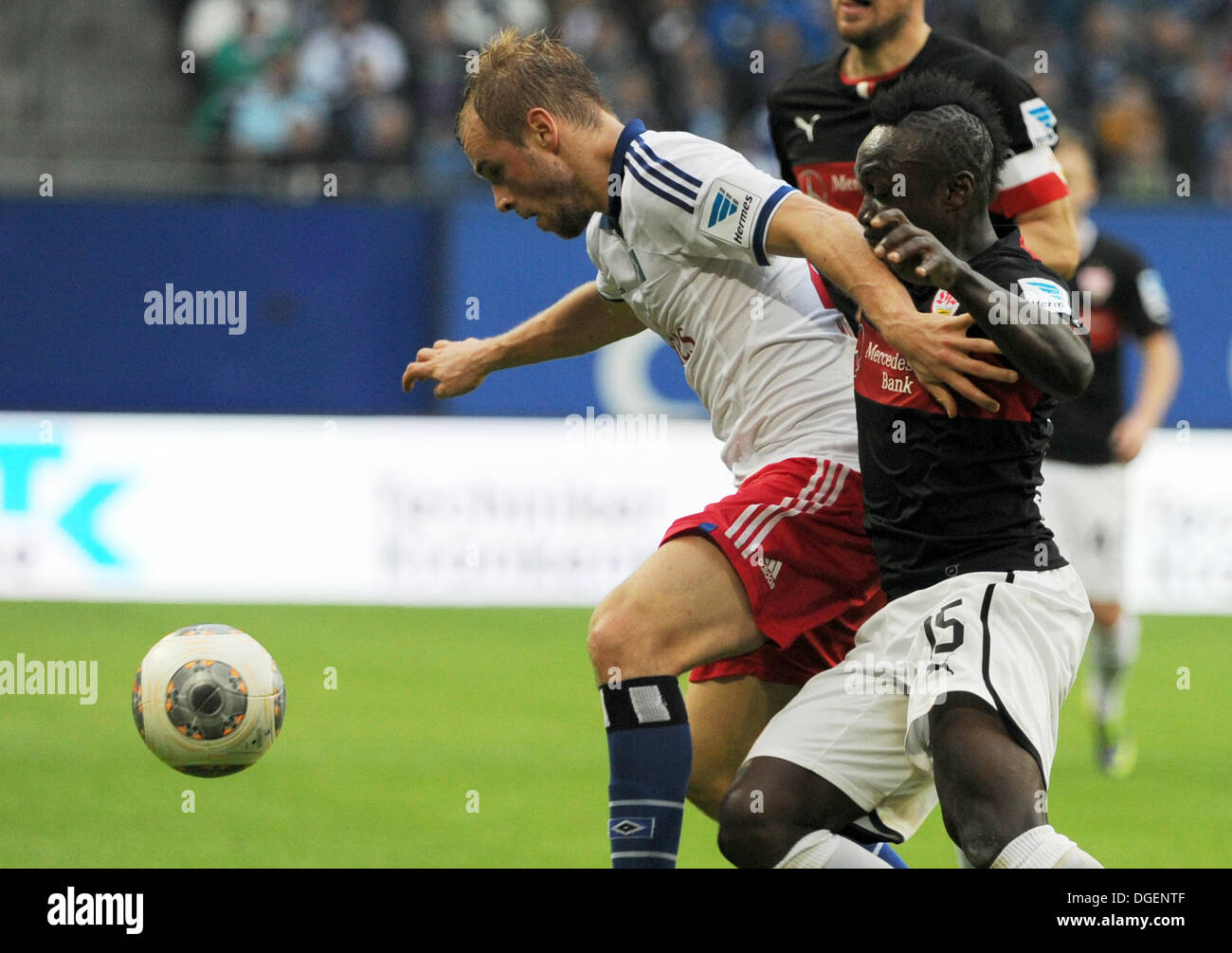 Hamburg, Germany. 20th Oct, 2013. Hamburg's Maximilian Beister (L) vies for the ball with Stuttgart's Arthur Boka (R) next to Stuttgart's Christian Gentner during the German Bundesliga soccer match between Hamburger SV and VfB Stuttgart at the Imtech Arena in Hamburg, Germany, 20 October 2013. Photo: ANGELIKA WARMUTH (ATTENTION: Due to the accreditation guidelines, the DFL only permits the publication and utilisation of up to 15 pictures per match on the internet and in online media during the match.)/dpa/Alamy Live News - Stock Image