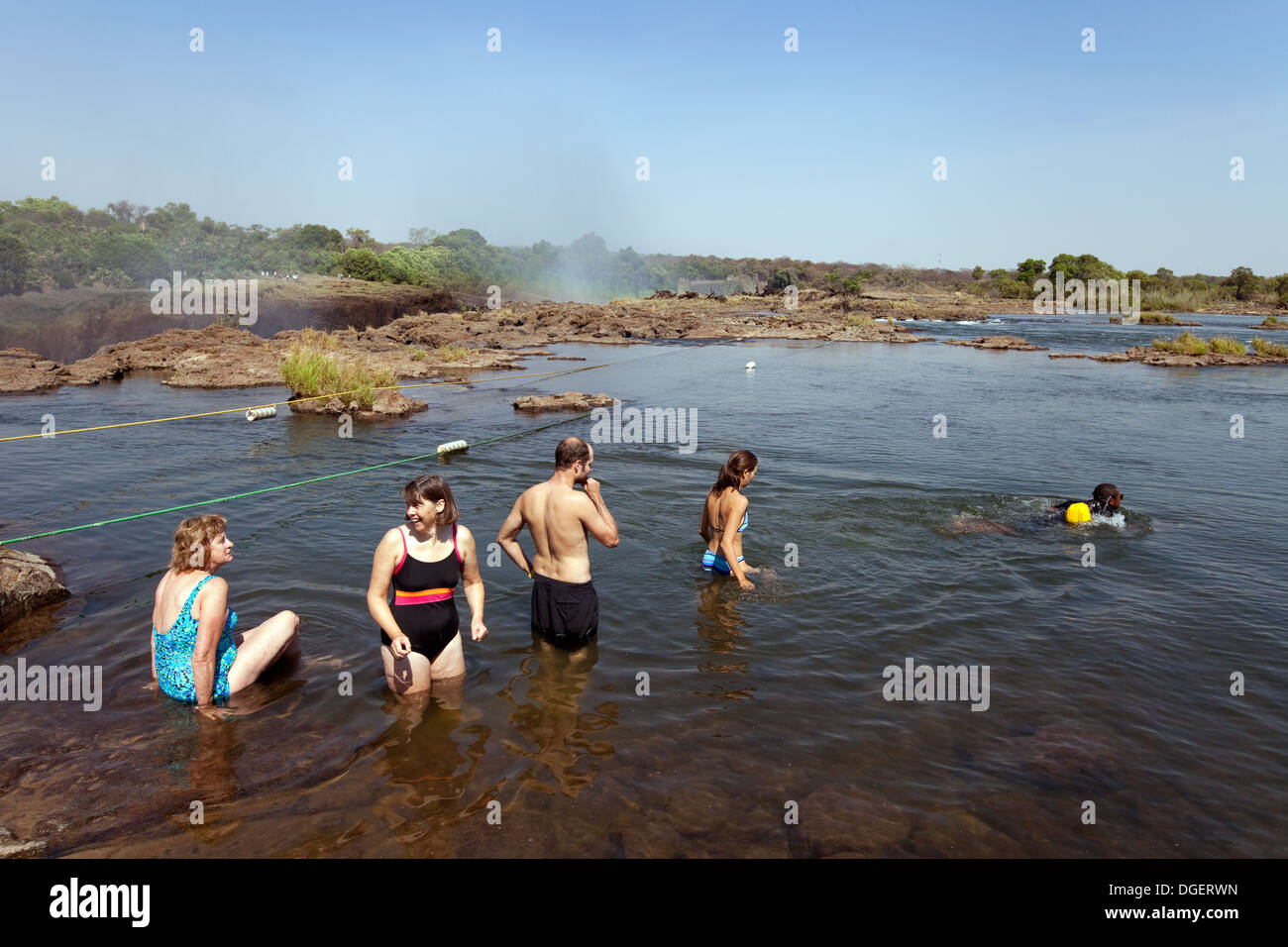 Tourists swimming out to Devils Pool at the edge of the Victoria Falls, Livingstone Island, Zambia africa - Stock Image