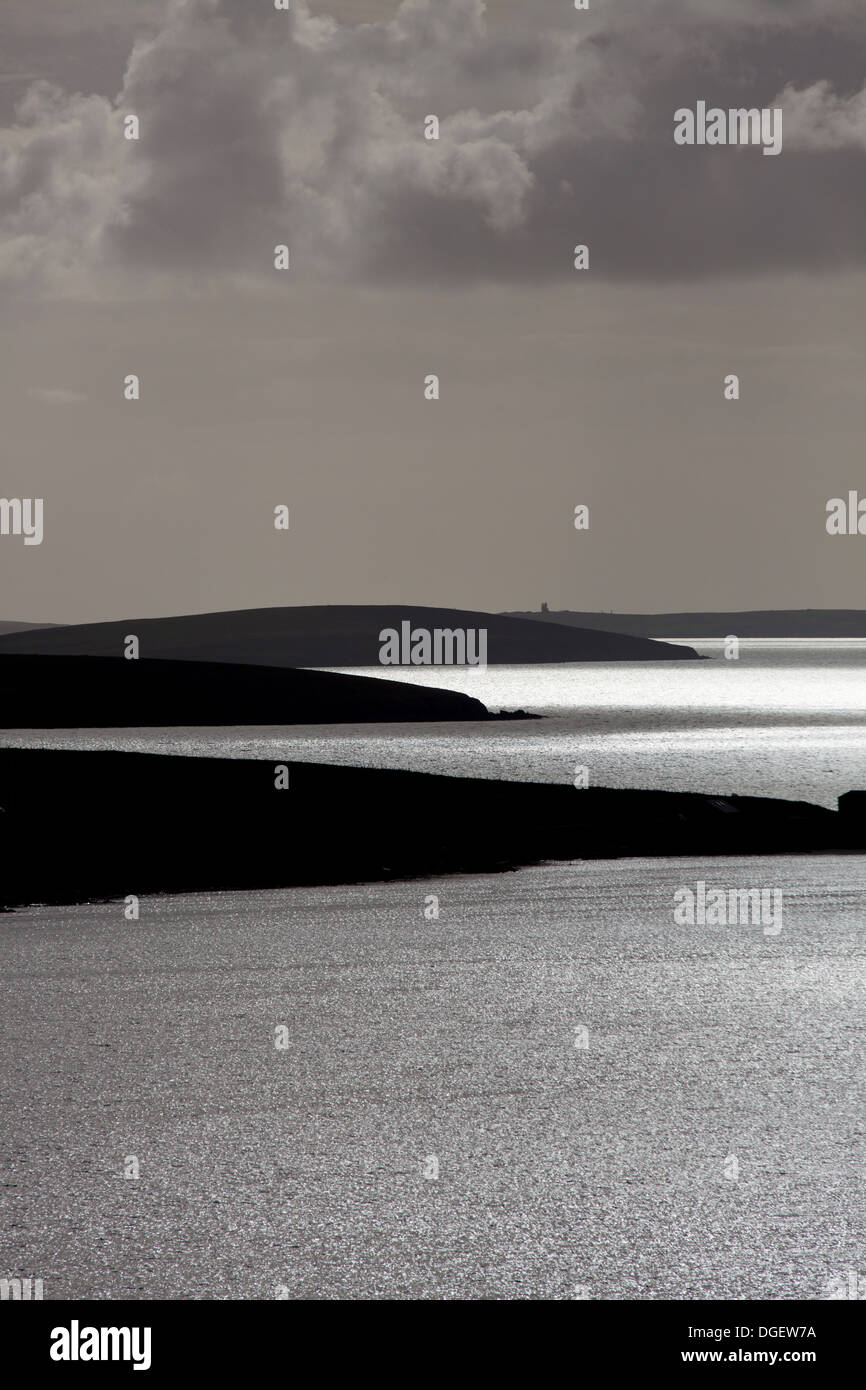Islands of Orkney, Scotland. Silhouetted view over the Orkney islands of Lamb Holm and Burray towards South Ronaldsay Stock Photo