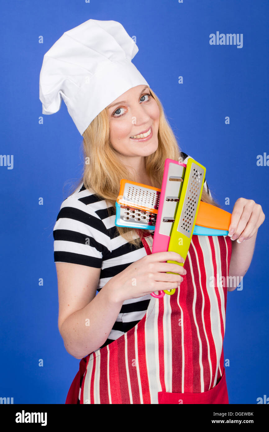 Model Released. Attractive Young Woman in Chefs Hat Holding Kitchen Utensils - Stock Image