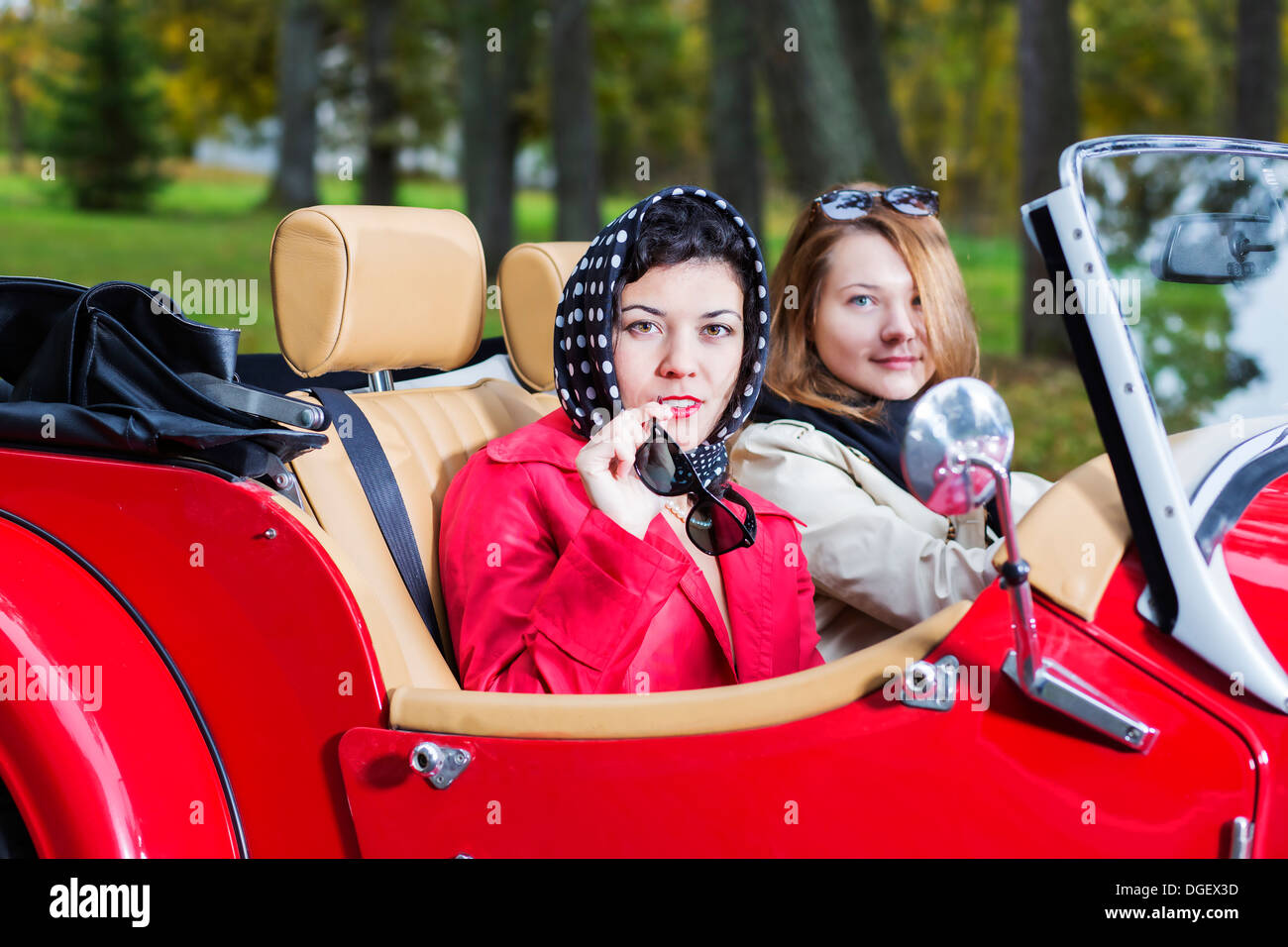 women at retro car look interested and satisfied - Stock Image