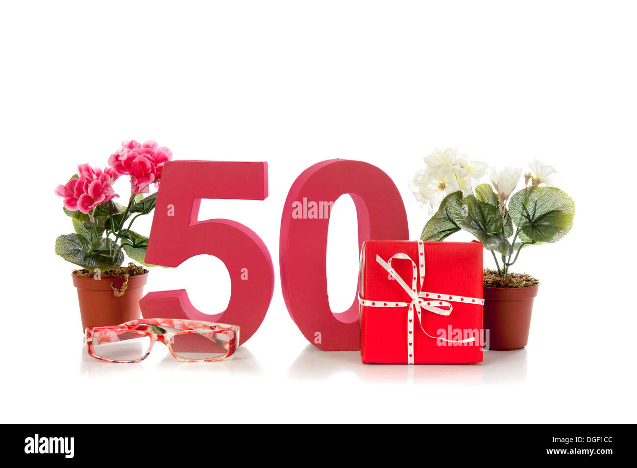 Celebrating your Fiftieth birthday, getting presents like reading glasses and a begonia - Stock Image