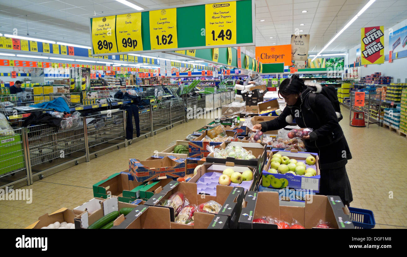 A woman shopping for fruit and veg looking at boxes of apples inside a German Lidl supermarket cheap food store in the UK  KATHY DEWITT - Stock Image