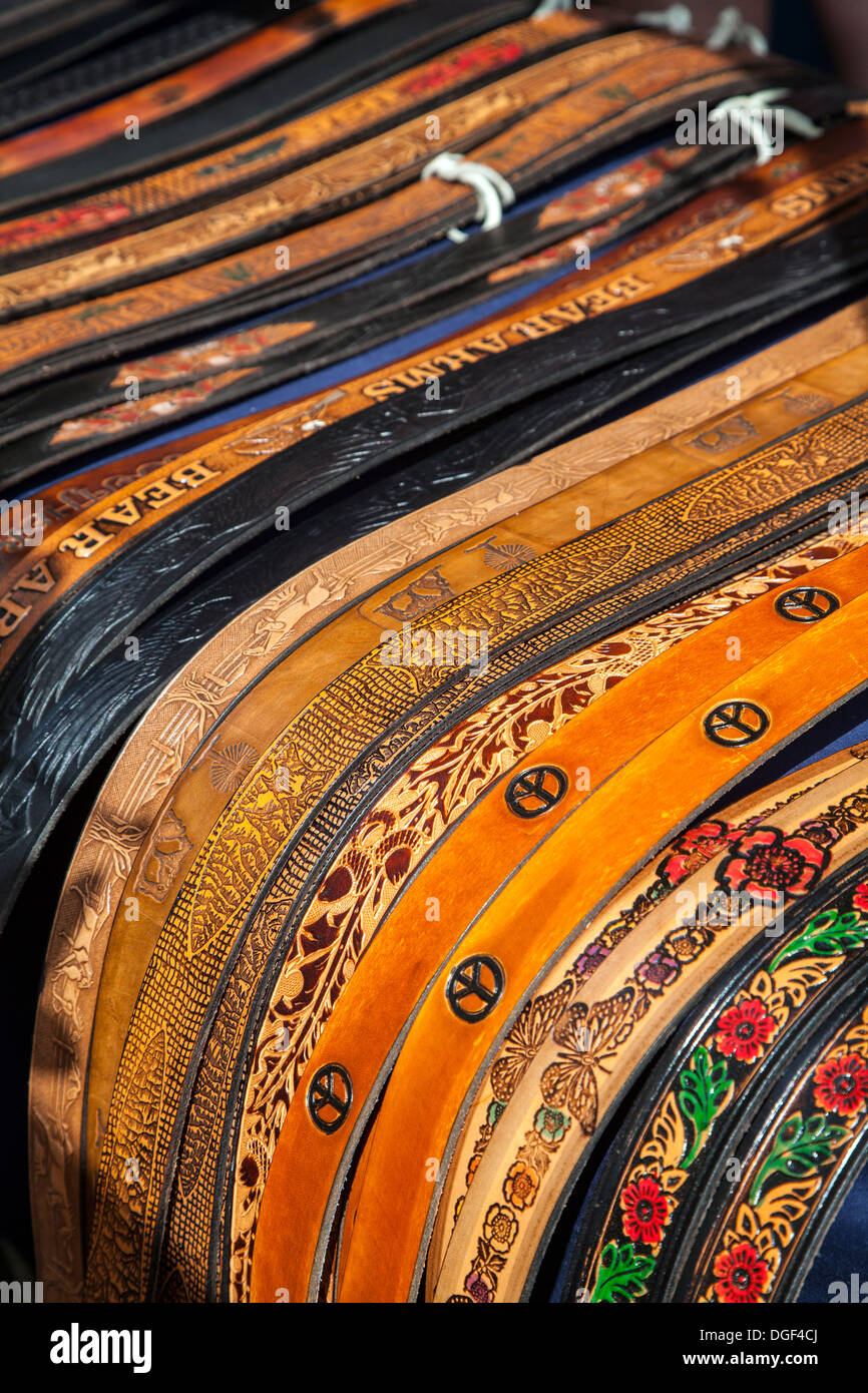 Colorful handtooled leather belts on display. - Stock Image