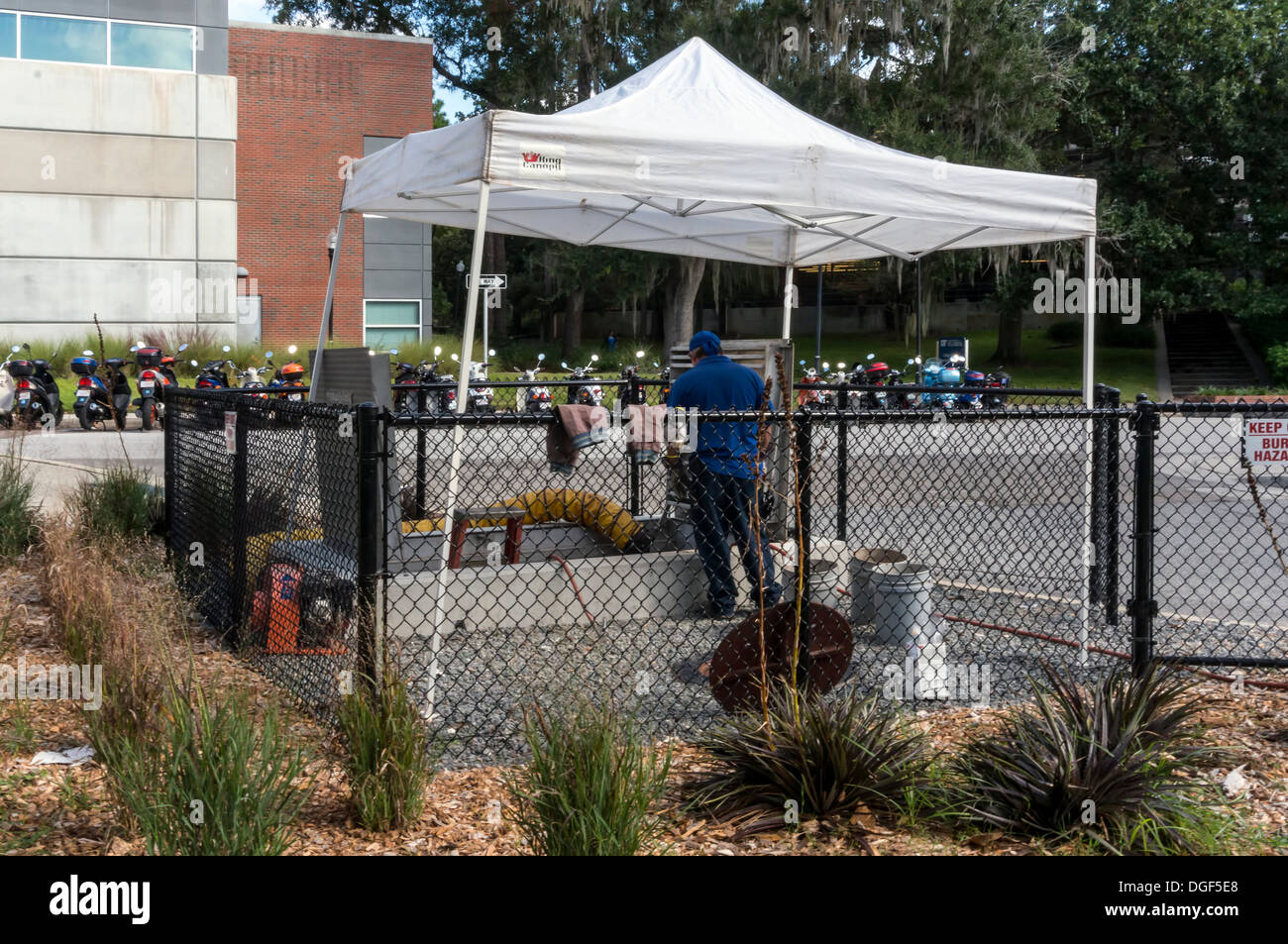 Utility worker working on underground utilities protected by a white canopy tent. - Stock Image