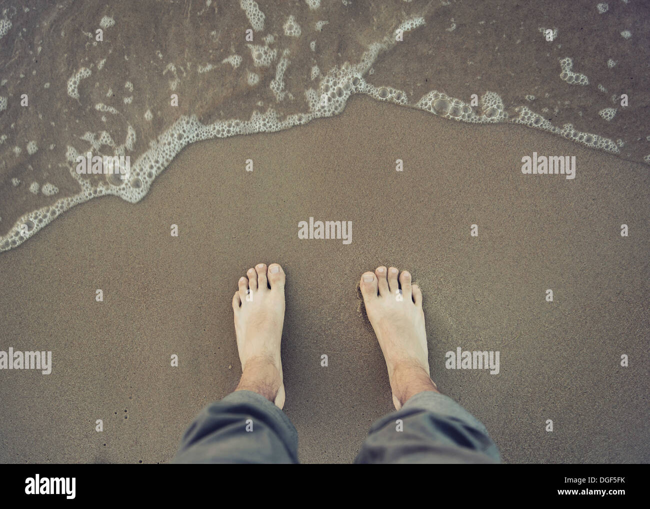 Photo of male bare foot near the sea water - Stock Image