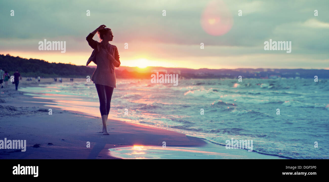 Alluring lady walking along the seaside - Stock Image