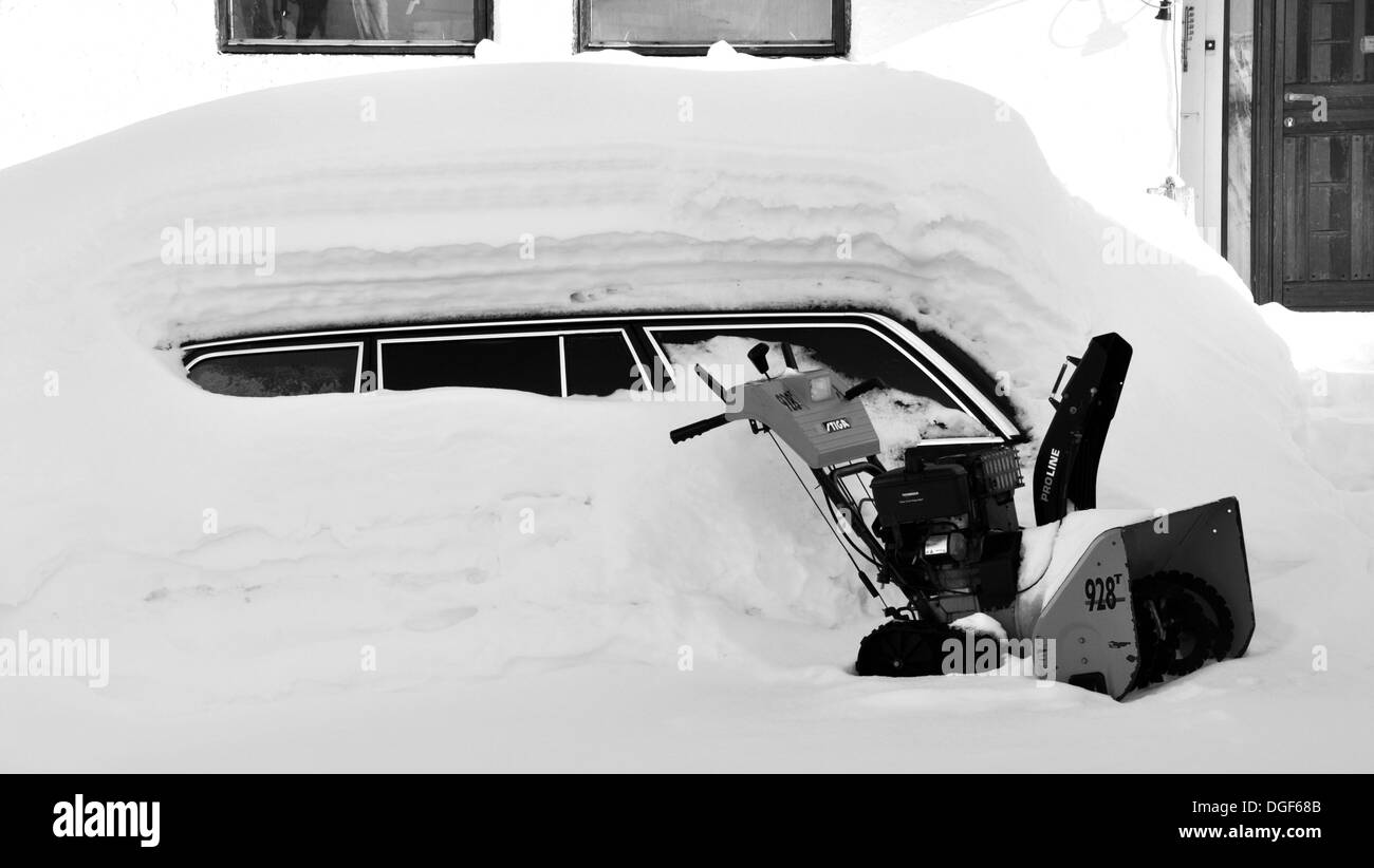 car covered with heavy snowfall,parked on street - Stock Image