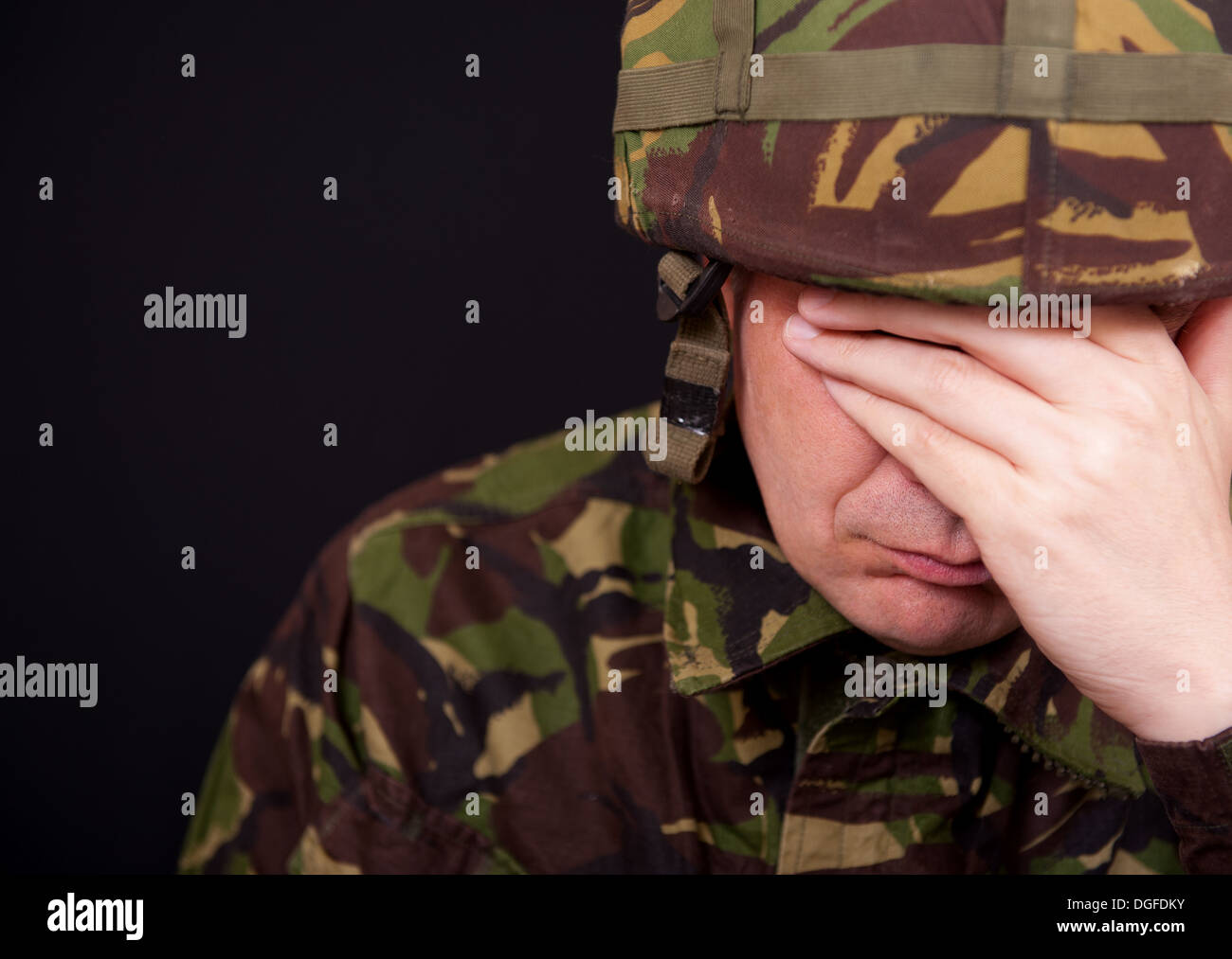 Soldier suffering with P.T.S.D./shell shock with his hand over his face. He wears British Military camouflage uniform. - Stock Image
