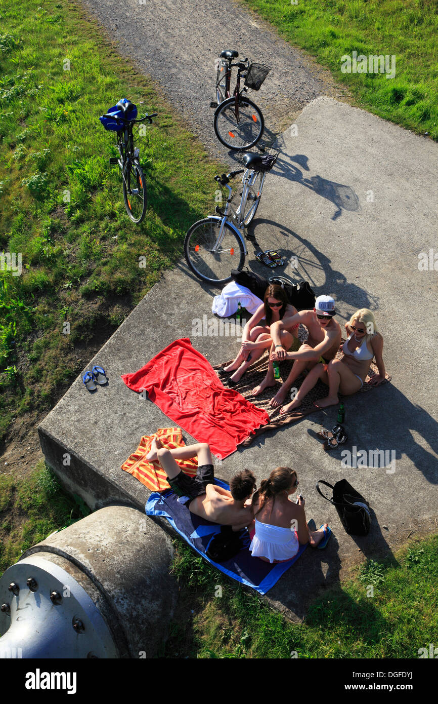 people, freetime, five youths, 16 to 18 years, two boys in bathing drawers and three girls in bikini sit on a bath towel and have a chat, next to it three bikes - Stock Image