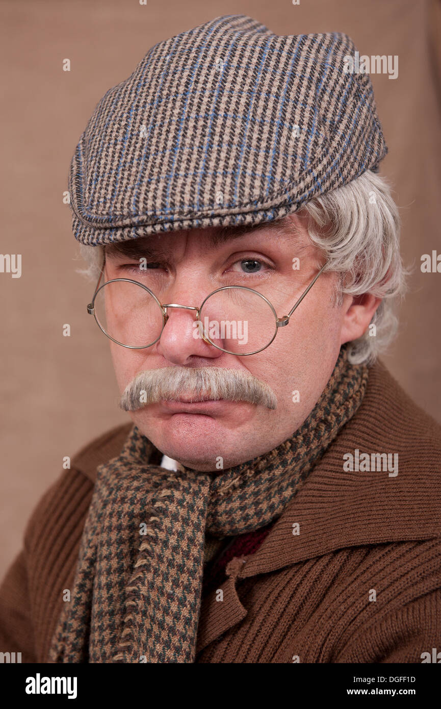 Portrait of a grey haired old man wearing flat cap and comfy scarf, against a brown background. - Stock Image