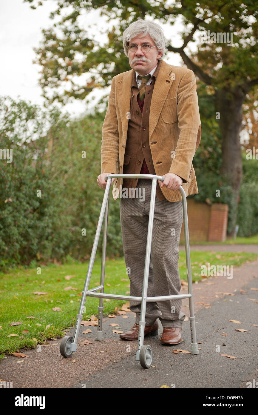 Grey haired old man walking along with his zimmerframe walking aid ...