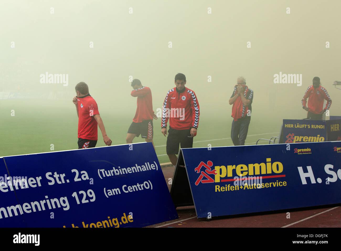 sports, football, Regional League West, 2013/2014, Rot Weiss Oberhausen versus Rot Weiss Essen 2:0, Stadium Niederrhein in Oberhausen, football fans of RW Essen firing smoke-bombs, fume, haze, mist, players and guardians with gum shields, danger to health - Stock Image