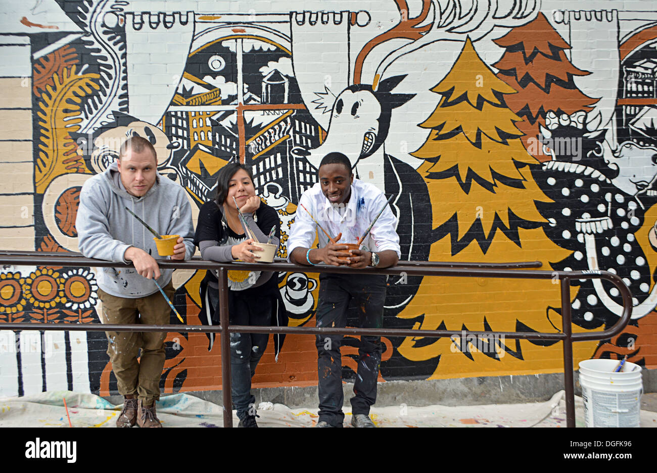 Portrait of 3 graffiti artists in front of a work in progress in Williamsburg, Brooklyn, New York - Stock Image
