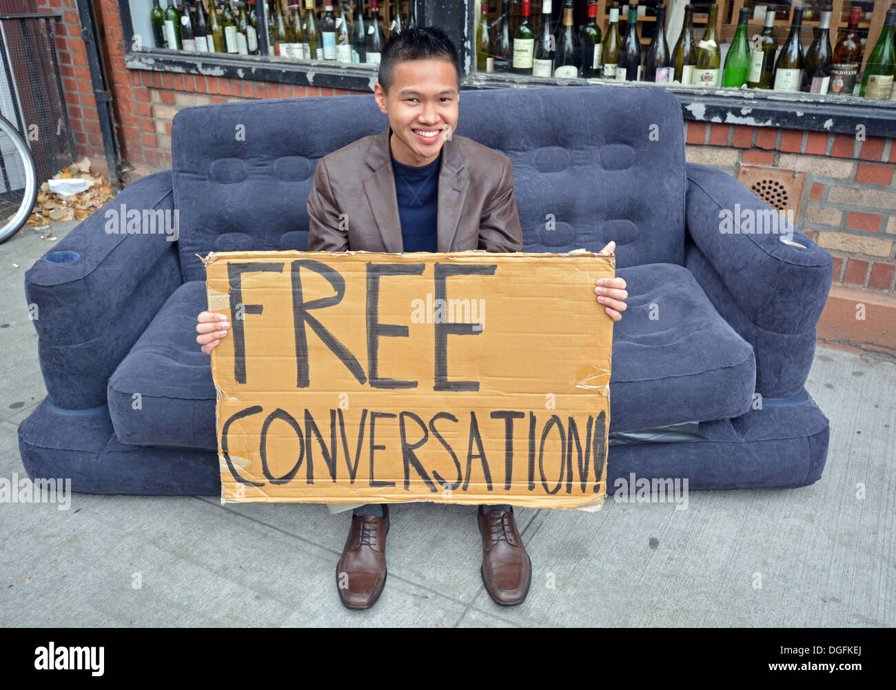 Portrait of Tony, 25, offering free conversation on a sofa in Williamsburg, Brooklyn, New York - Stock Image