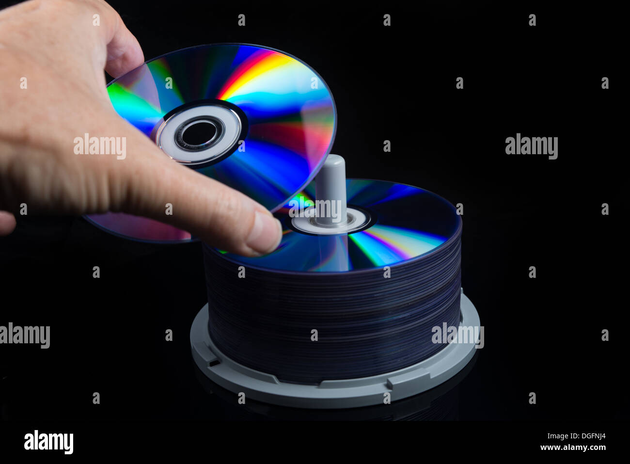 hand picking a dvd from a stack, cd, blu ray, - Stock Image