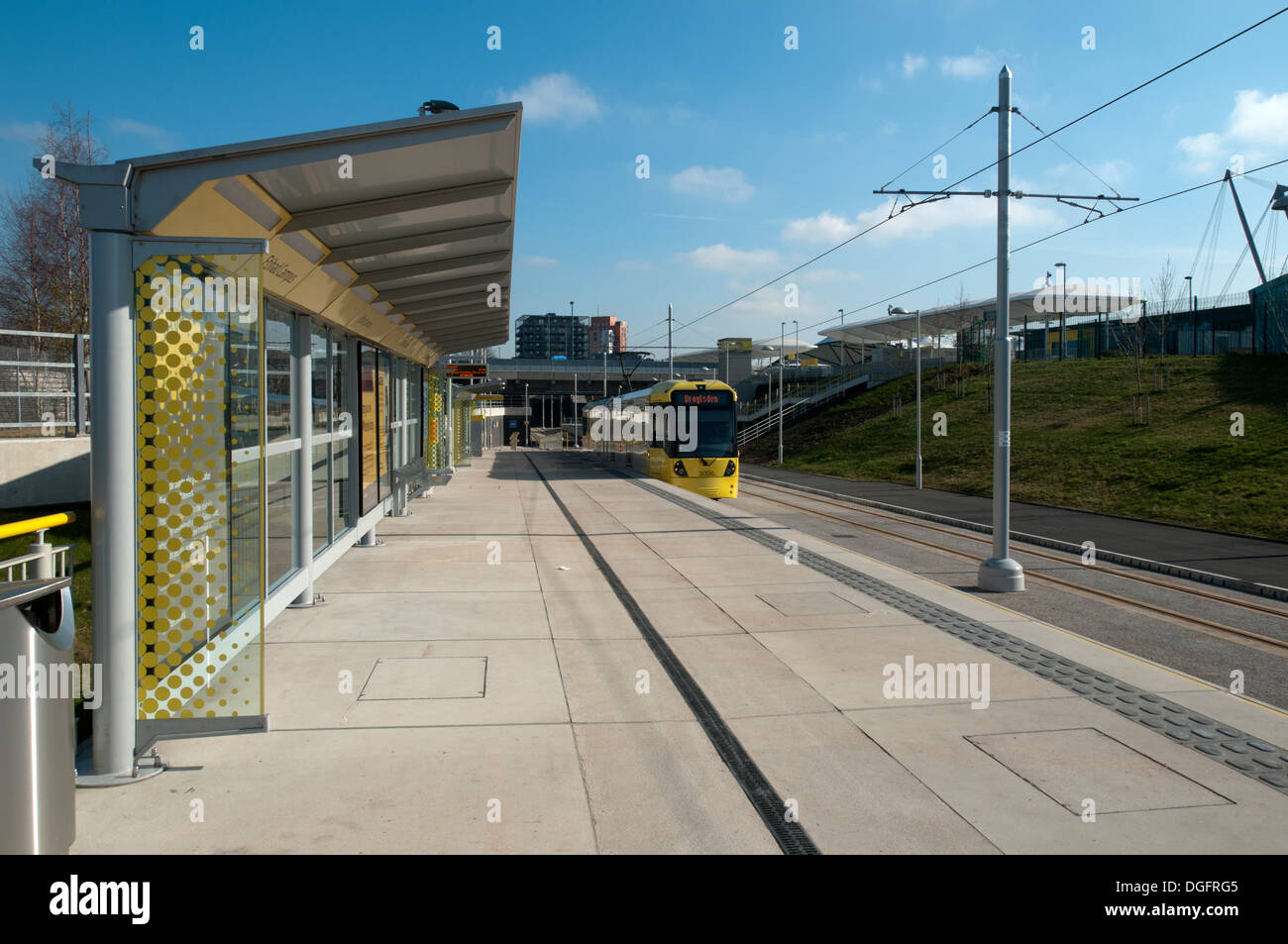 Metrolink tram at the Etihad Campus stop, on the East Manchester Line, Eastlands, Manchester, England, UK - Stock Image