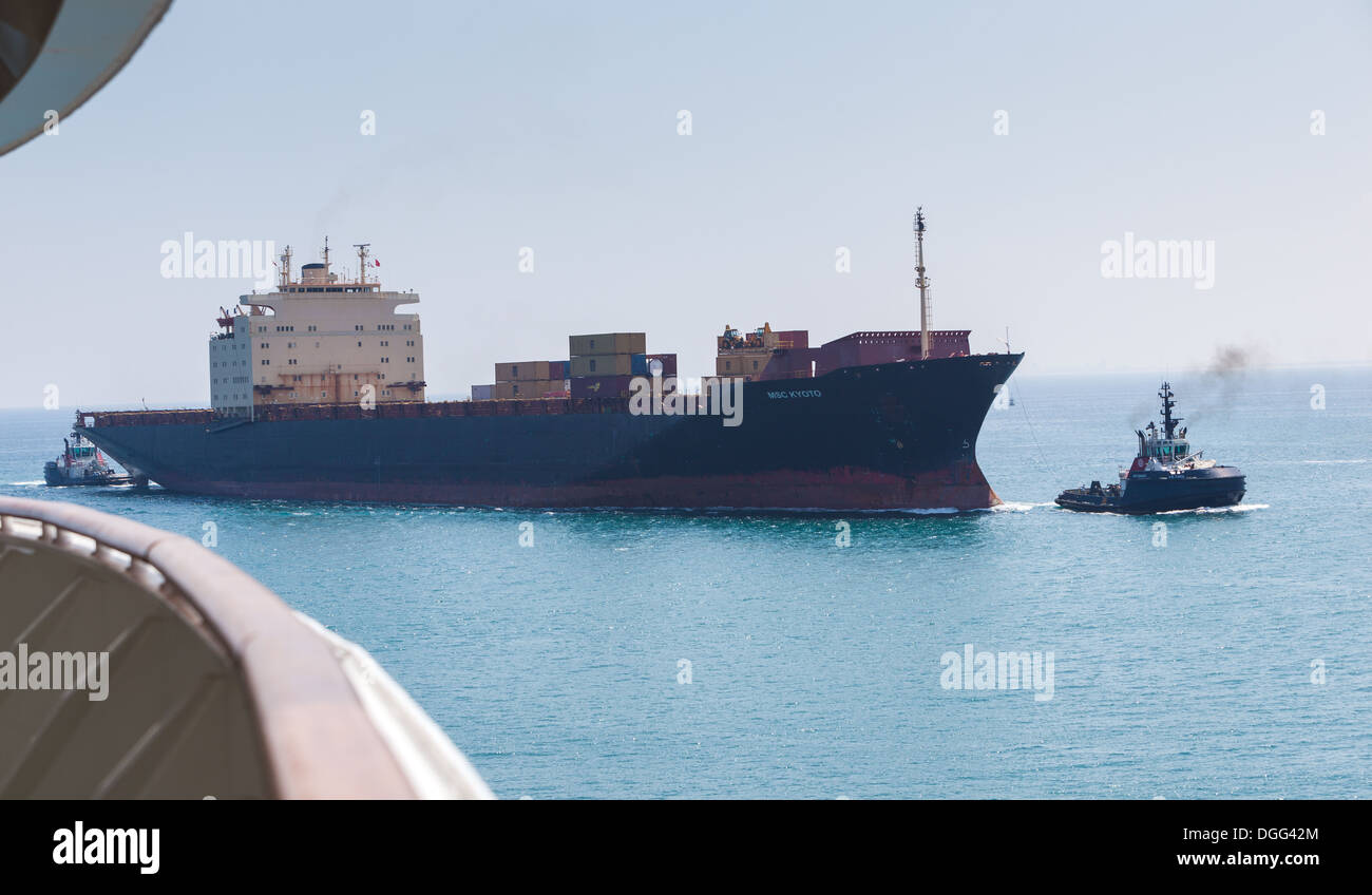 """Container ship """"MSC KYOTO """" entering Valencia harbour Spain with tugs assisting Stock Photo"""