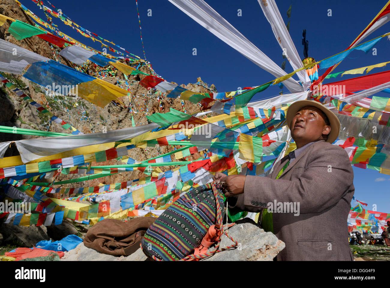 Tibetan pilgrim amid newly put up prayer flags for upcoming ceremony, Namtso Lake, Heavenly Lake, Tibet, China, Asia - Stock Image