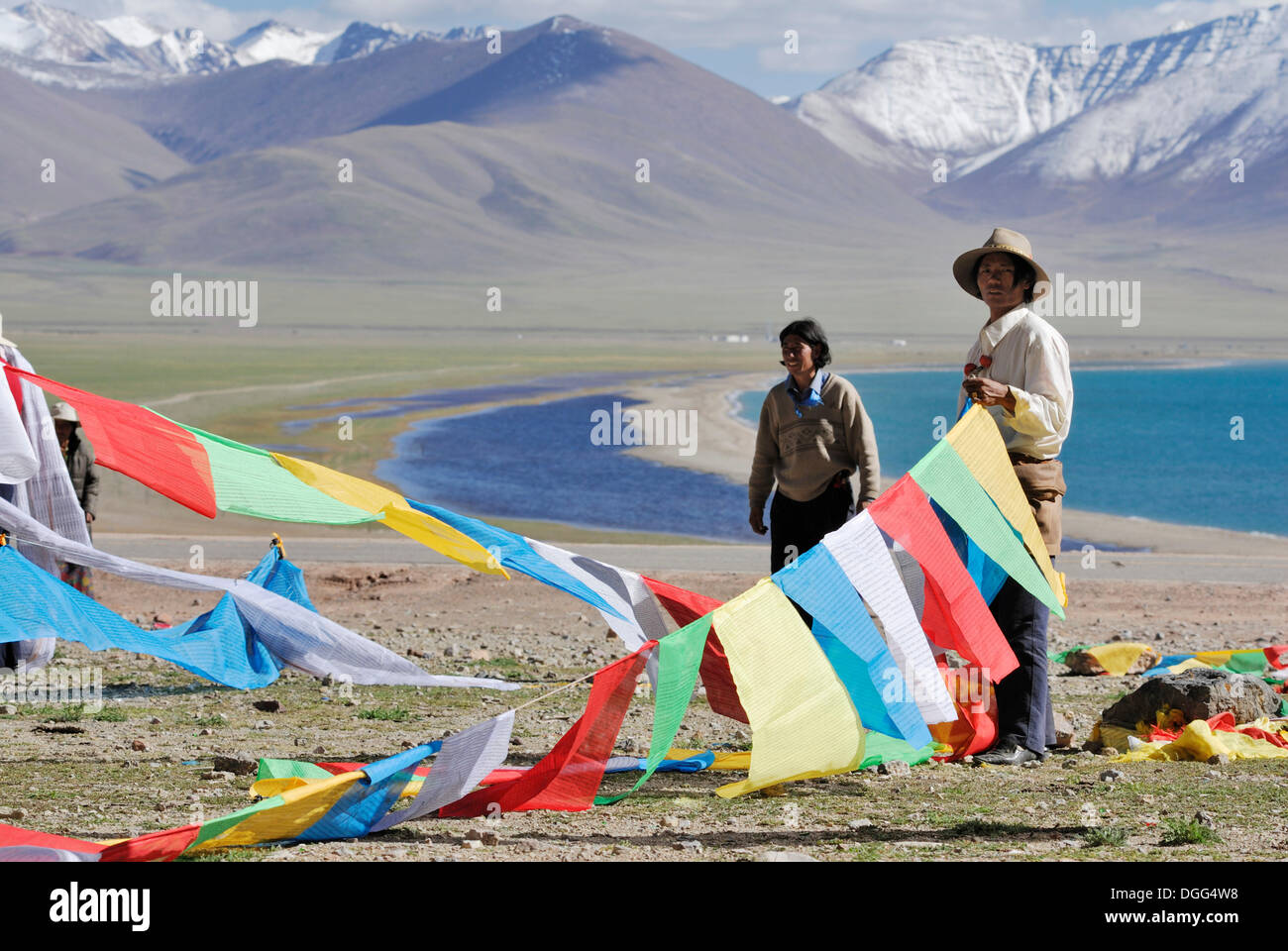 Tibetan pilgrims hanging prayer flags for the upcoming ceremony at Namtso Lake, Heavenly Lake, Tibet, China, Asia - Stock Image