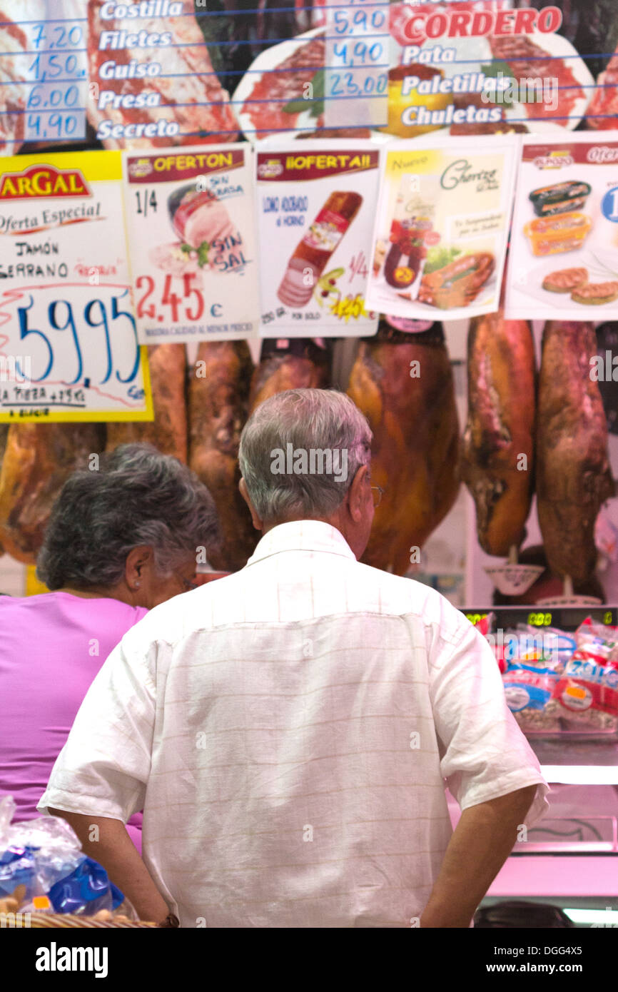Elderly couple at market  butcher shop counter Valencia Spain - Stock Image