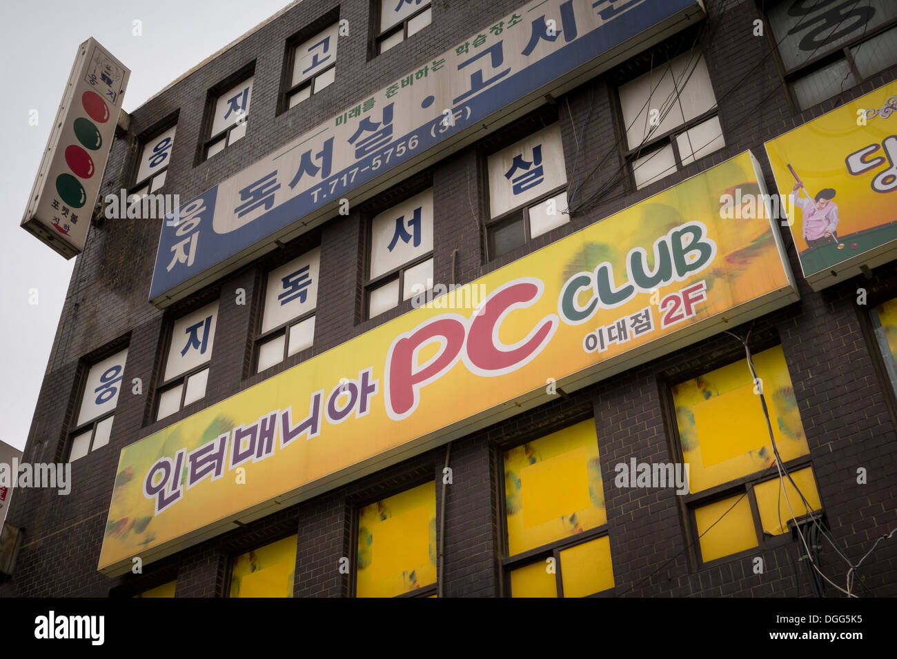 PC Bang sign (yellow) on a building in Seoul - Stock Image