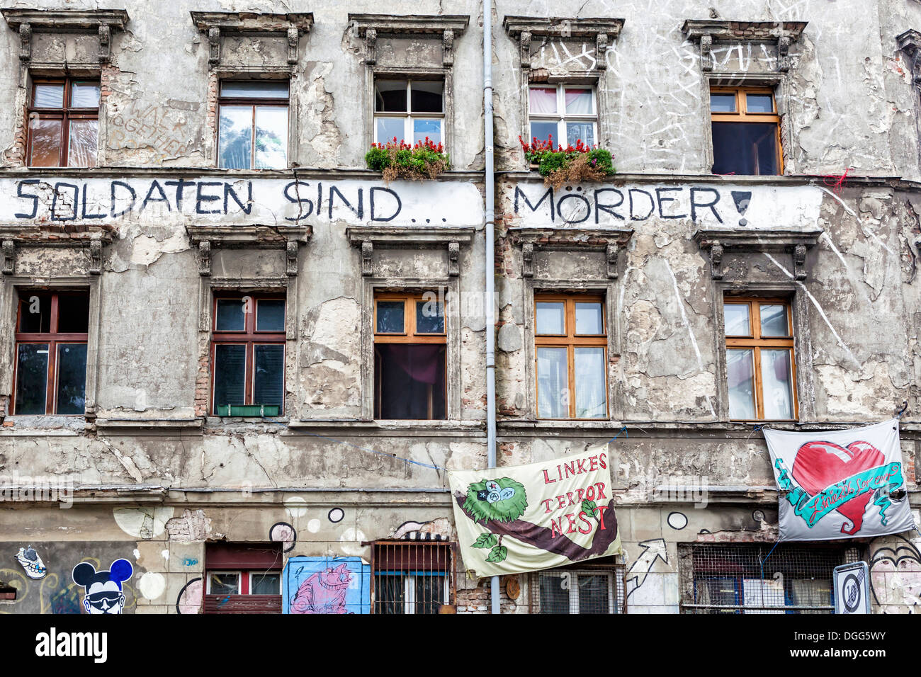 Exterior of derelict building covered in graffiti, stickers and posters occupied by squatters - Mitte Berlin - Stock Image