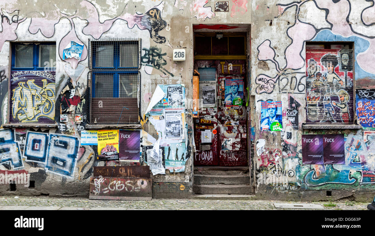 Derelict building covered in graffiti, stickers and posters occupied by squatters - Mitte Berlin - Stock Image