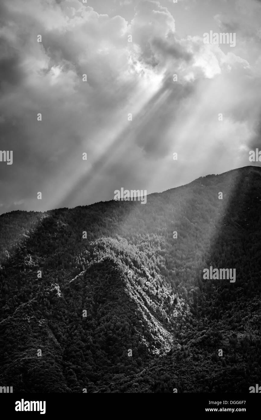 Sun rays through the clouds illuminating mountains. - Stock Image