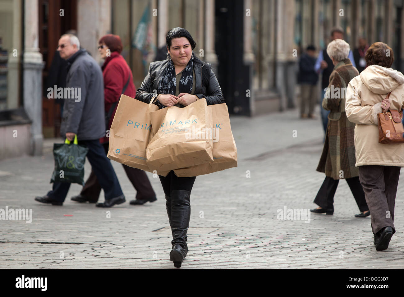 A woman shopper walks through Liverpool City Centre carrying Primark shopping bags - Stock Image