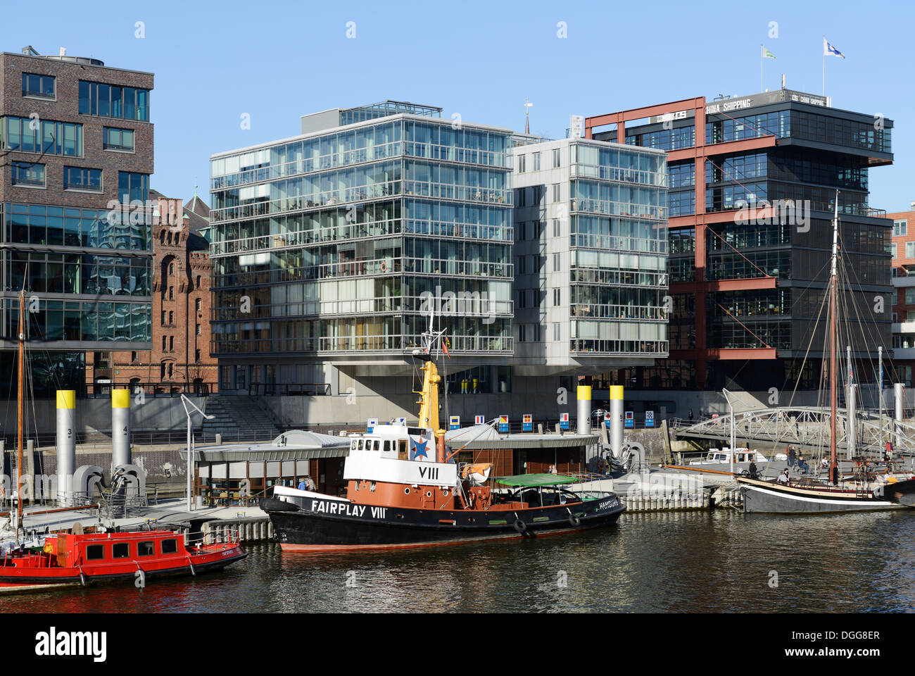 Sailing ship and tug Fairplay VIII in the historic harbor, modern residential and office buildings, Sandtorkai, Sandtorhafen - Stock Image