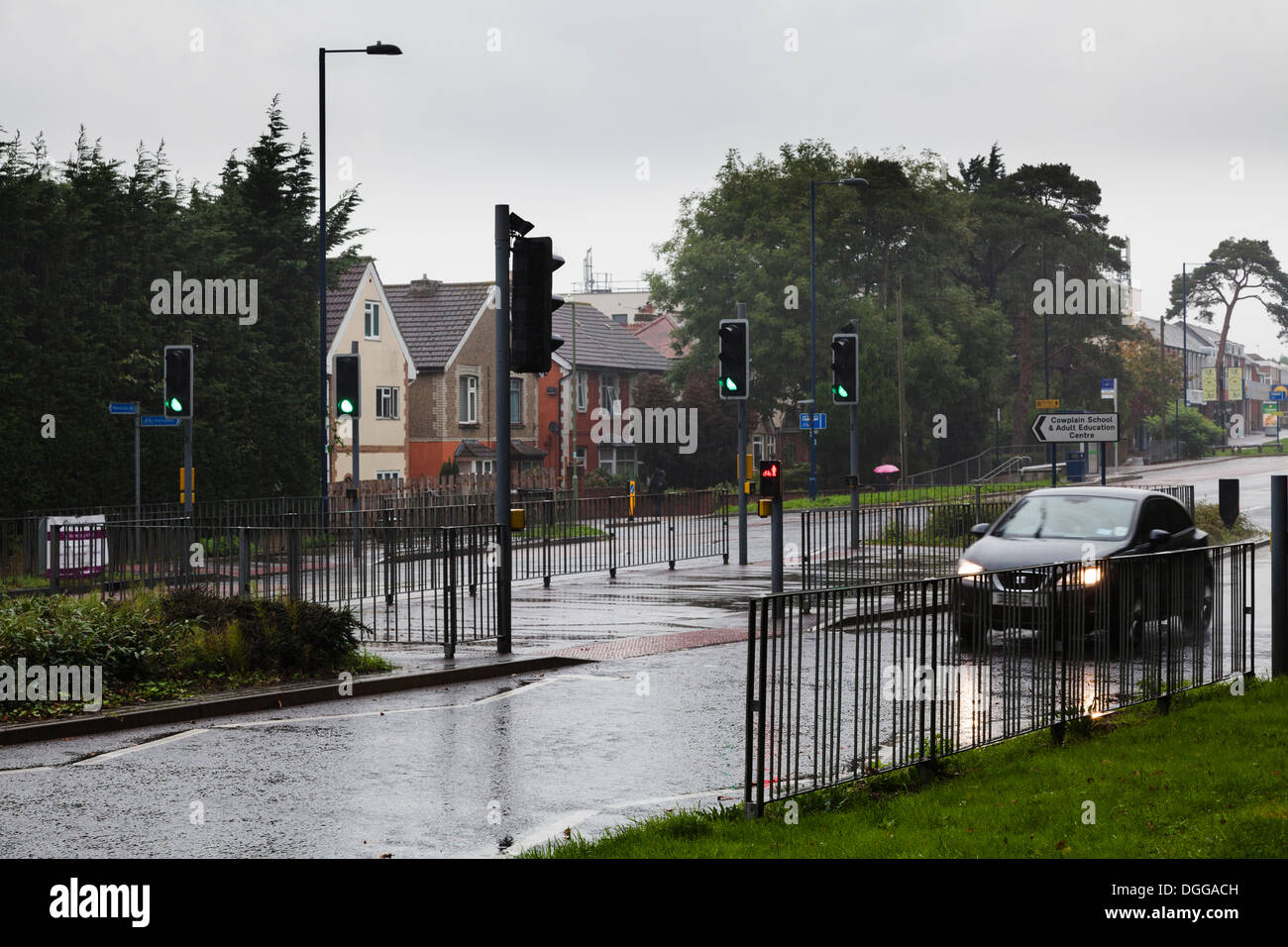 car on rainy road with lights controlled staggered pedestrian pelican crossing - Stock Image