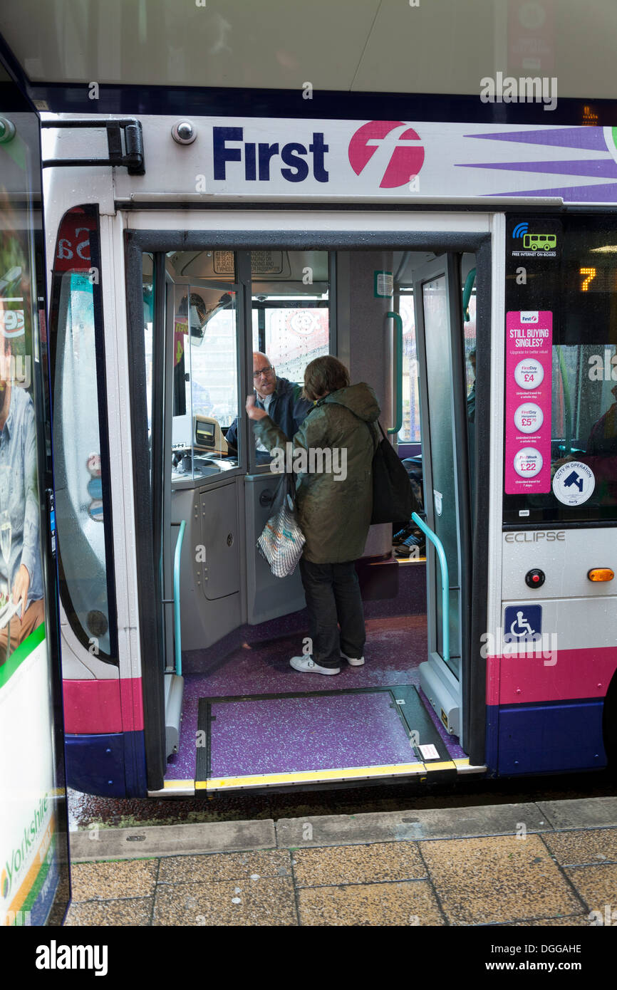 Passenger talking to driver on First public bus at bus stop. - Stock Image
