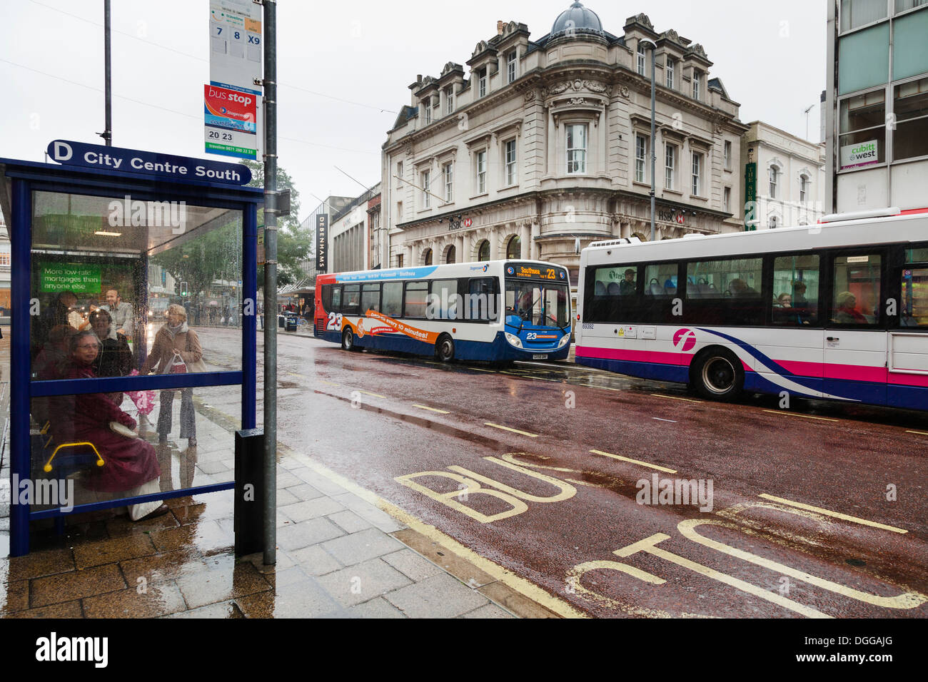 passengers waiting in town centre bus shelter with single decker buses - Stock Image