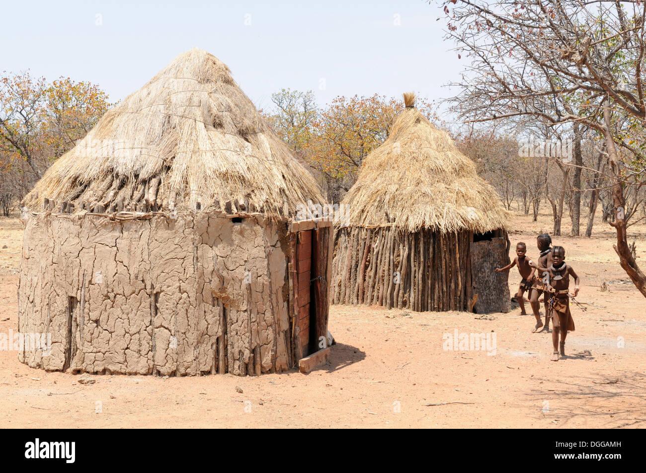 Himba children playing outside Himba huts in a Himba village, Kamanjab, Kunene Region, Namibia - Stock Image