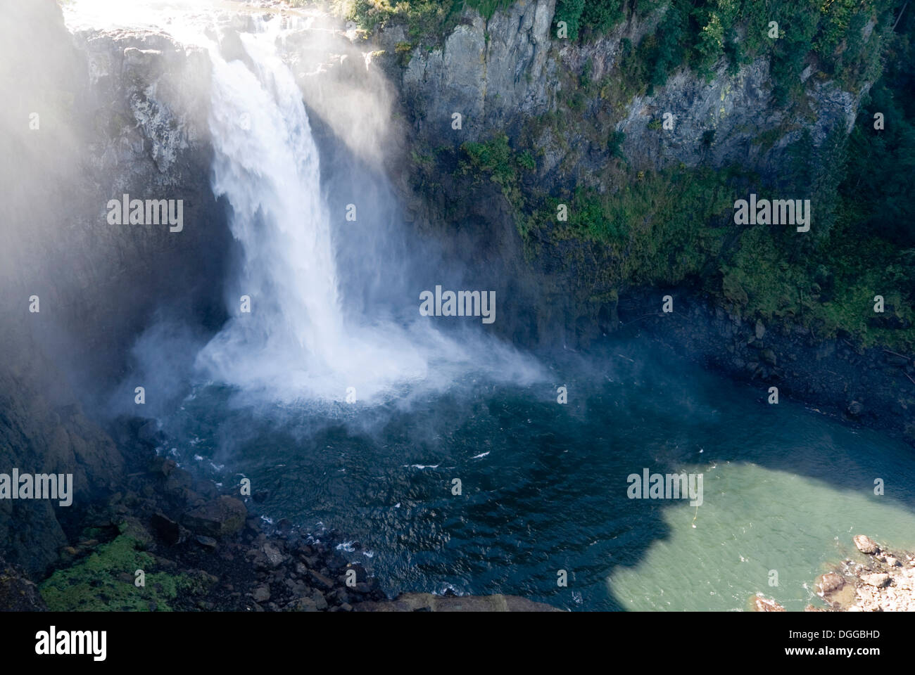Water pouring over the top of Snoqualmie Falls waterfall into a natural river canyon, Washington State, USA Stock Photo