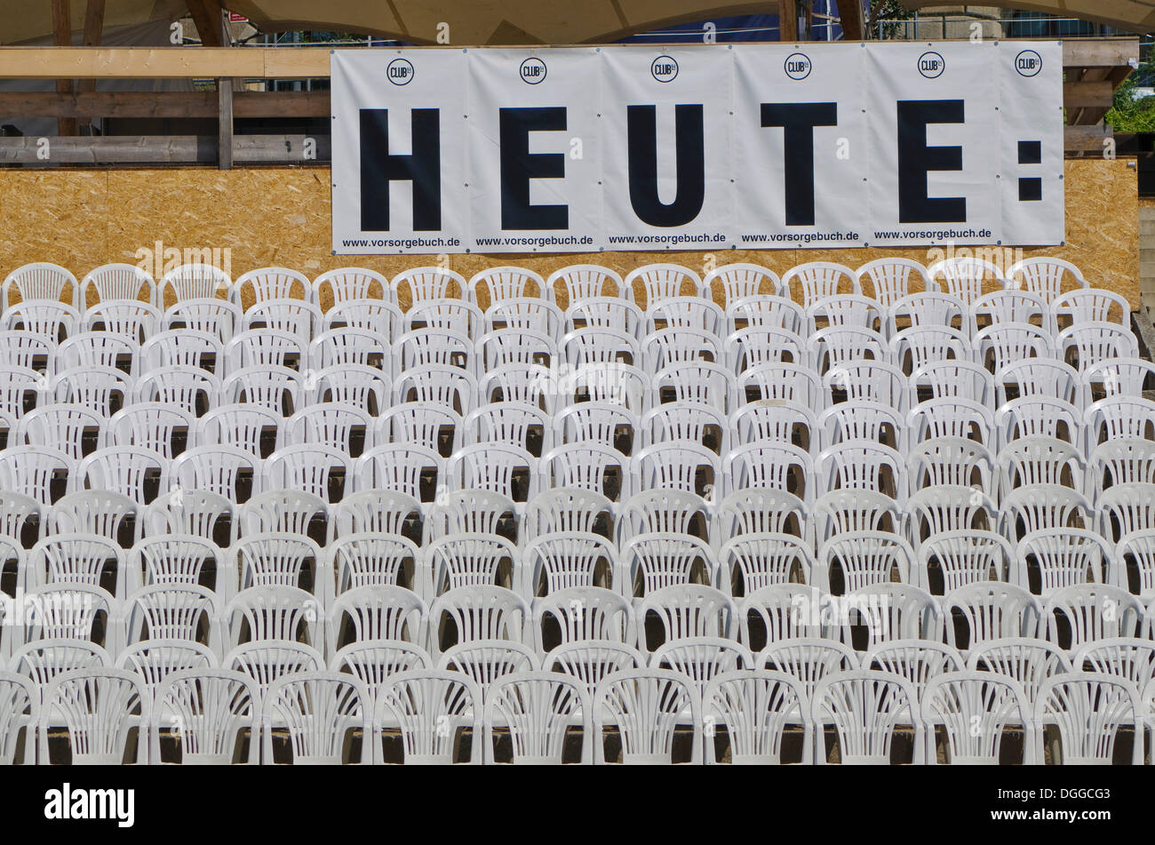 Sign 'heute', German for 'today', and white plastic chairs arranged in rows at an open air concert area, Dresden - Stock Image