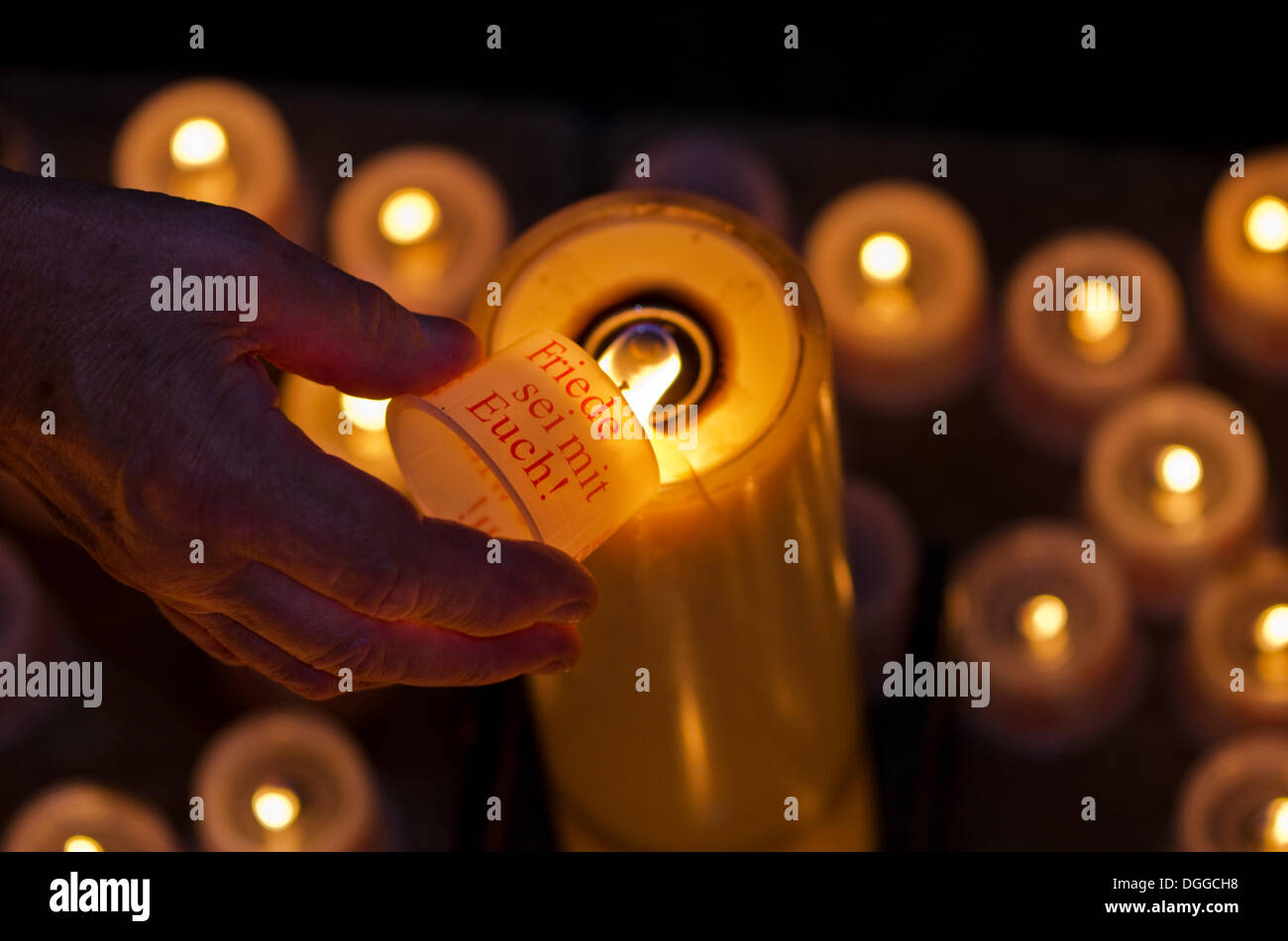 Hand of a devotee lightening a candle for offering inside the Frauenkirche church, Dresden, Saxony - Stock Image