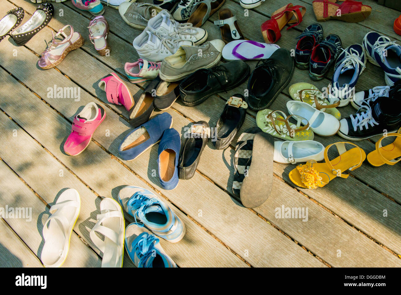 Large group of shoes on wooden planks - Stock Image