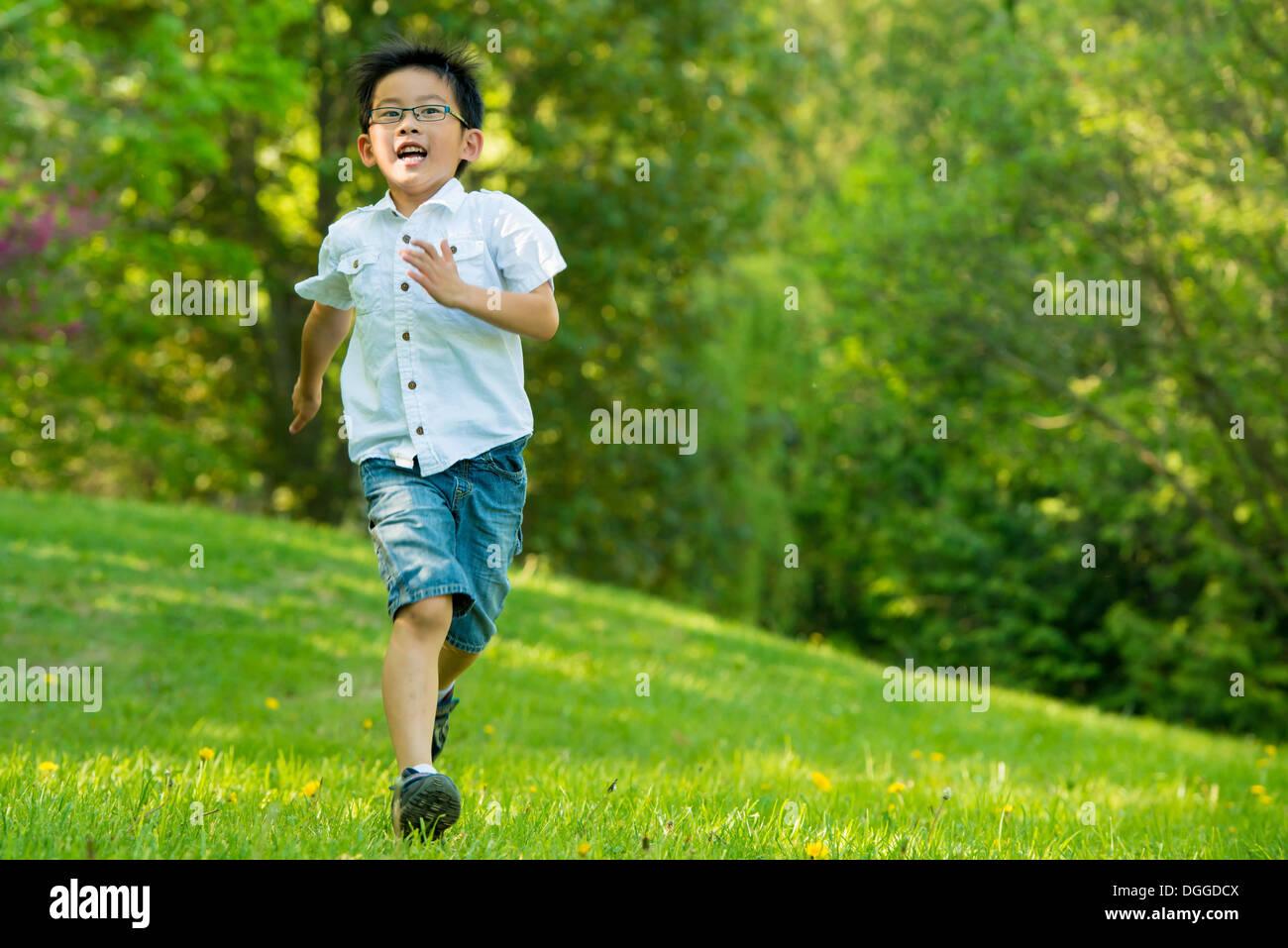 Boy running on grass - Stock Image