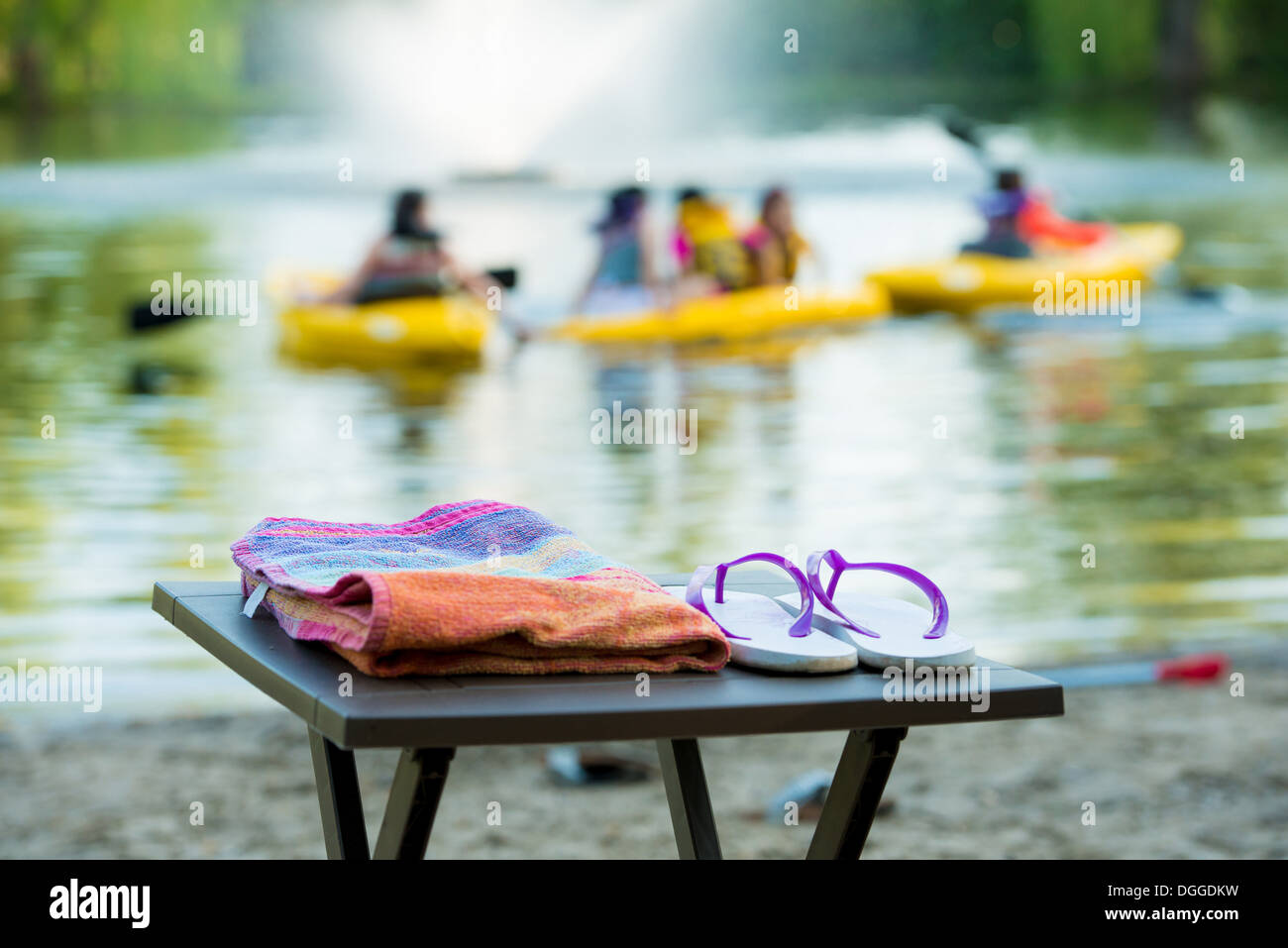 Flip flops and towel on table by lake - Stock Image