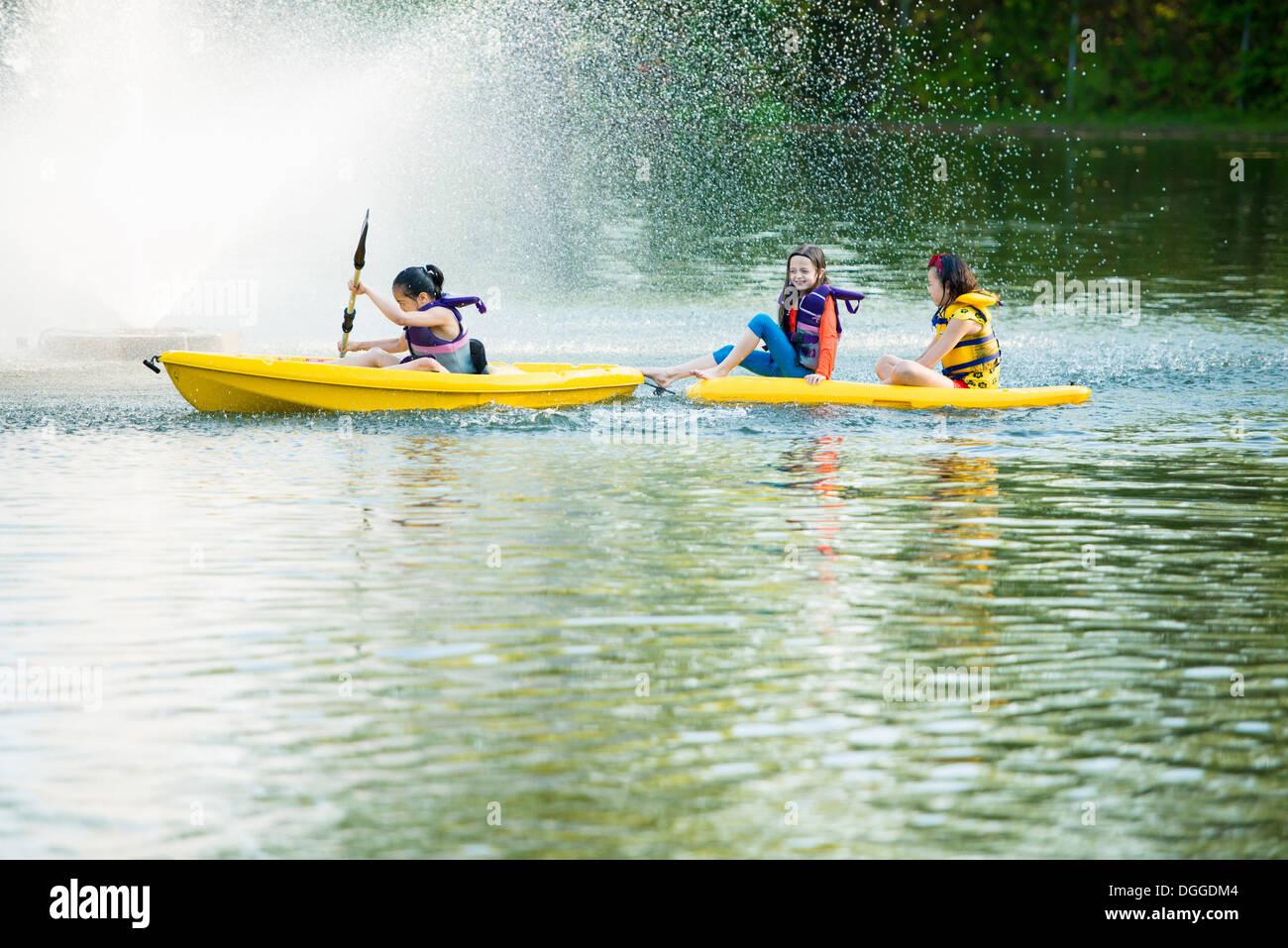 Girls canoeing on lake - Stock Image