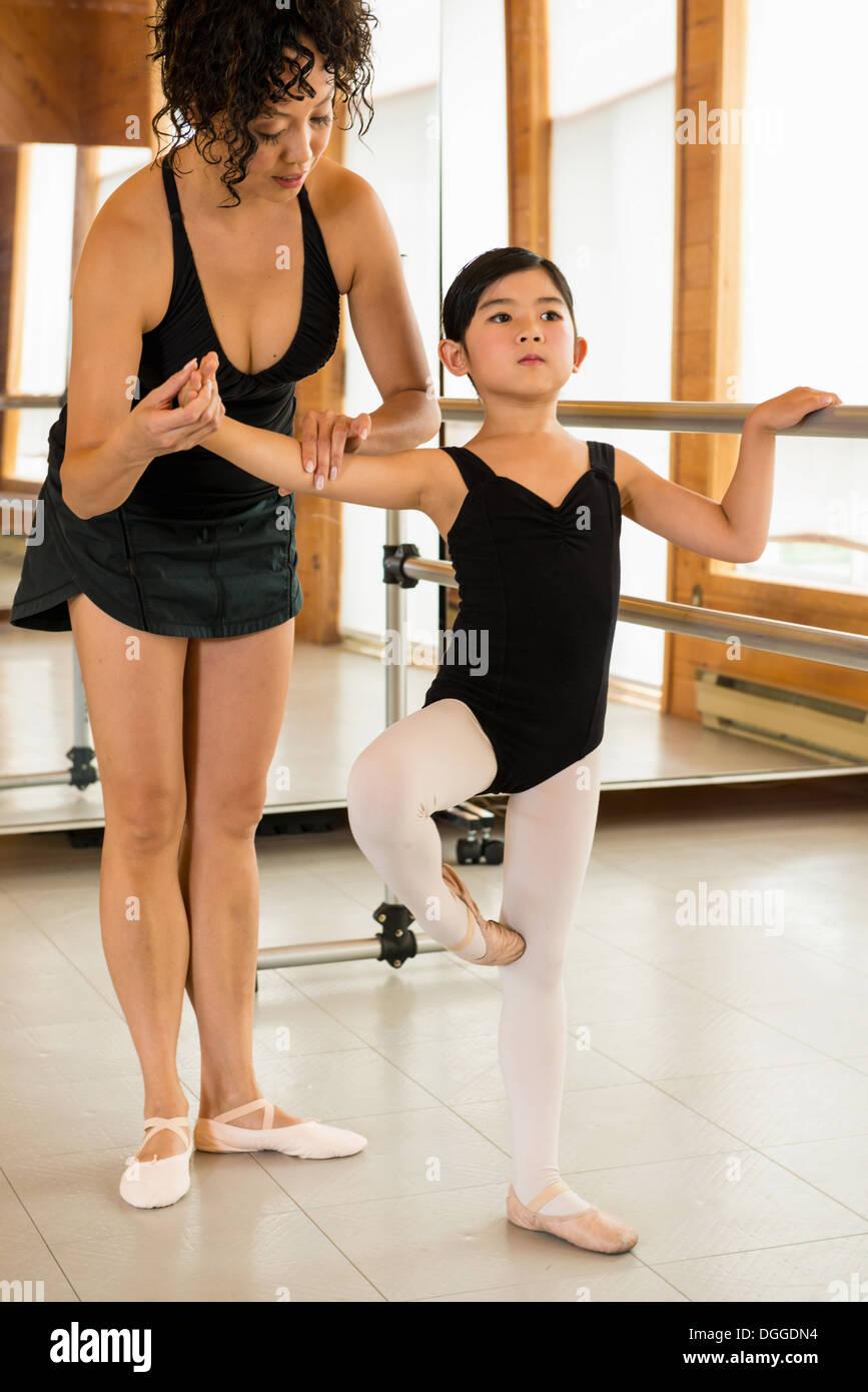 Mature woman teaching ballet dancers in studio - Stock Image