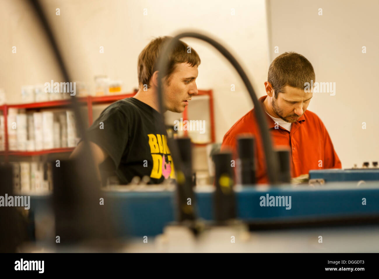 Man watching supervisor in screen print workshop - Stock Image